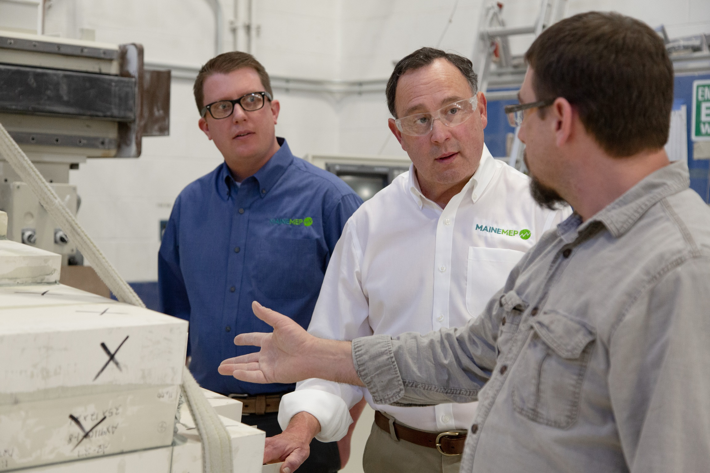 Project Managers speaking with client in manufacturing facility